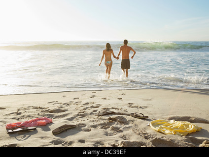 Couple holding hands and wading in ocean - Stock Image
