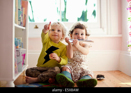Female and male toddler friends pointing and looking up - Stock Image