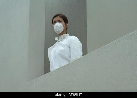 Femme portant un masque de pollution et une combinaison de protection, faible angle de vue - Image