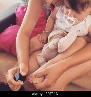 Mother nail polish to the small daughter - Stock Image