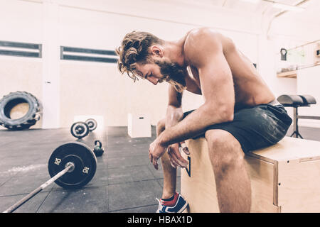 Exhausted male cross trainer taking a break from weightlifting in gym - Stock Image