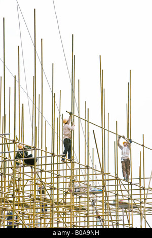 Construction workers on scaffolding, low angle view - Stock Image