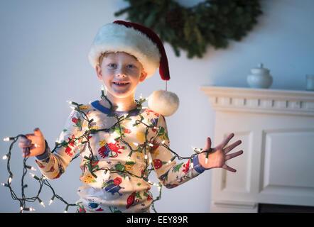 Portrait of boy (6-7) holding christmas lights - Stock Image