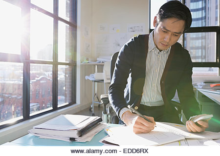 Architect drafting plans in sunny office - Stock Image