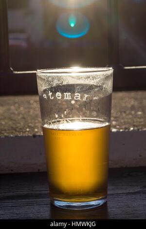 Une pinte de bière Batemans Gold avec la lumière du soleil qui brille à travers elle - Image