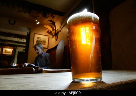 Une pinte d'amer se tenant sur une vieille table en bois dans un pub anglais. Un homme est assis à une table derrière. - Image de l'éditeur