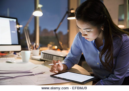 Businesswoman with digital tablet working late in office - Stock Image