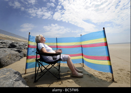 A  OLD AGE PENSIONER ENJOYS SUNBATHING ON A BRITISH BEACH WITH WINDBREAKER RE HOLIDAYS RETIREMENT OAPS PENSIONERS - Stock Image
