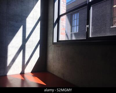 Sunlight shining through a window on a concrete wall - Stock Image