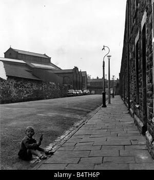Cardiff Old Adamsdown A young child sits in the gutter in Cycle Street with the abattoir pictured on the left 20th - Stock Image