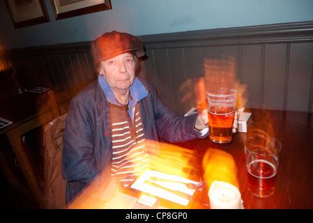 Femme à la recherche excentrique lève une pinte de bière dans un pub, Londres, Angleterre, Royaume-Uni (synchro lente) - Image
