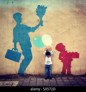Little boy facing camera tries to reach for the balloon painted on the wall - Stock Image