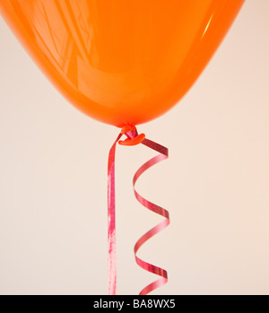 Orange balloon and ribbon - Stock Image