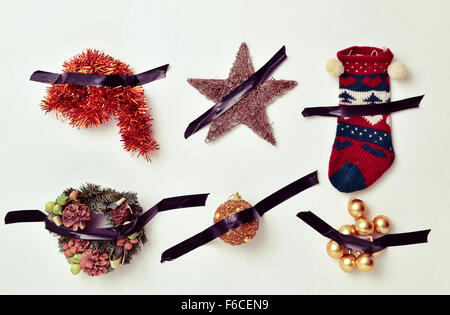 some different christmas ornaments, such as tinsel, a star, a stocking or baubles, attached to a white wall with - Stock Image