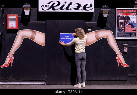 Hamburg, Germany. 14th May, 2019. A woman hangs a sign with the inscription 'Hier wählt Europa' on the entrance door of the boxing ring 'Zur Ritze' on the Hamburg Reeperbahn. The initiative #SayYesToEurope wants to mobilise for the EU election and offers the possibility to fill in the postal voting documents brought along at special places. Credit: Axel Heimken/dpa/Alamy Live News - Stock Image