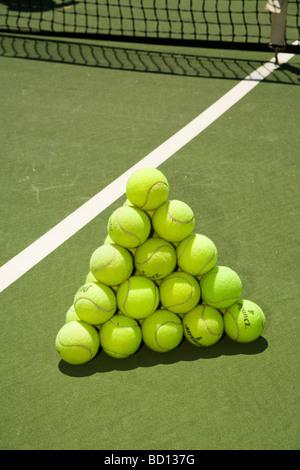Les balles de tennis sont empilées pour former un tétraèdre régulier. - image d'archive