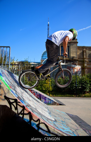 BMX biker performing tricks on a ramp - Stock Image