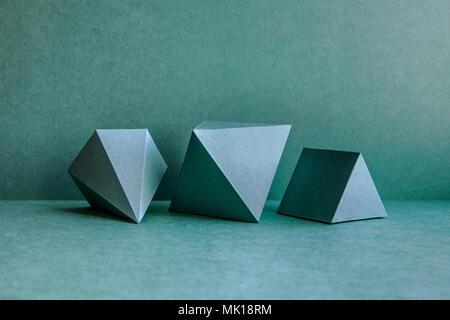 Figures géométriques encore composition de la vie. Objets de cube rectangulaire tétraédrique de pyramide prisme en trois dimensions sur fond vert. Solides platoniques - image d'archive