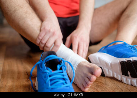sportsman massaging his injured ankle after a sport accident - Stock Image