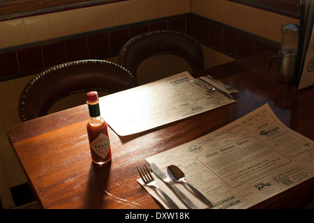 Diner condiments sit on the table in a small town diner.  Place mats advertise local businesses. - Stock Image