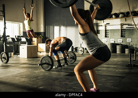 People training with barbells and gymnasium rings - Stock Image