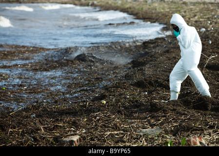Personne en tenue de protection, marchant le long du rivage pollué - Image