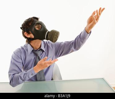 Homme d'affaires, assis dans la salle blanche, portant masque à gaz gesticulant à une personne inconnue - Image
