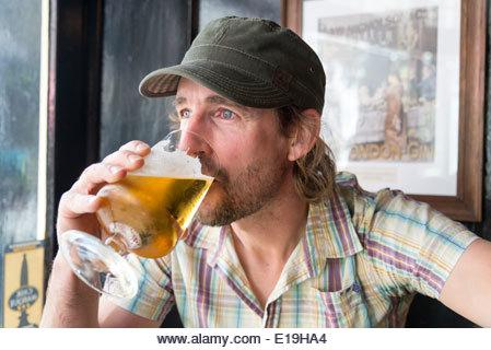Homme buvant une pinte de bière dans un pub, Angleterre, Royaume-Uni - Image