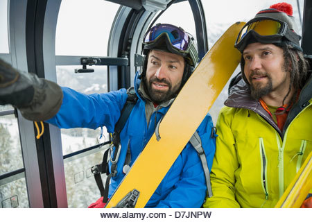 Male skiers talking in gondola in mountains - Stock Image