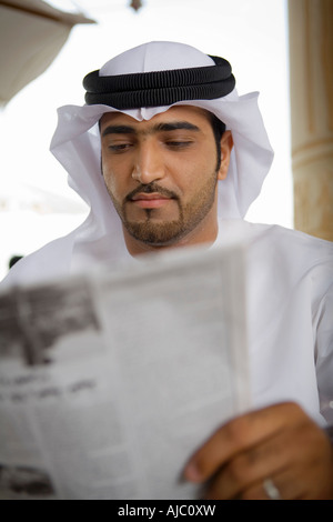 Arab Business Man Reading Newspaper on Patio - Stock Image