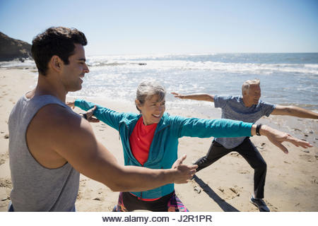 Crossfit trainer helping senior couple exercising, practicing yoga warrior 2 pose on sunny beach - Stock Image