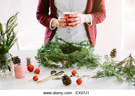 Woman decorating Christmas wreath - Stock Image