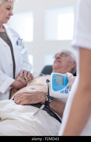 Senior man doing chek up in hospital, looking worried - Stock Image