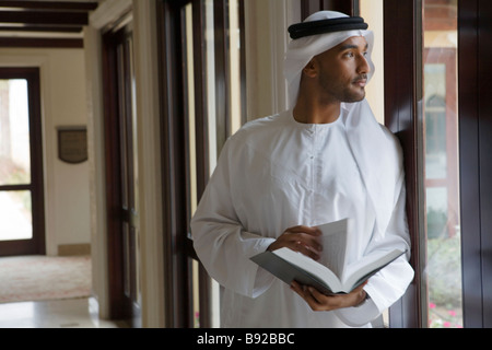 Arab man looking out a window holding a book - Stock Image