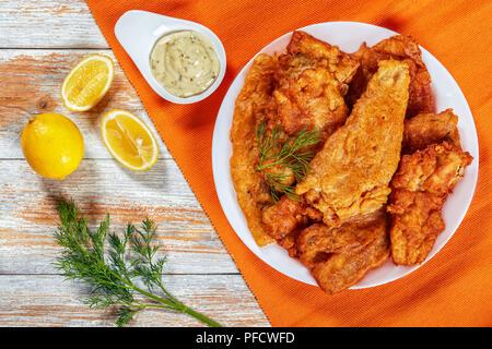 délicieux croustillants poêlés à la bière Filets de poisson de mer battus sur un plateau blanc sur une vieille table en bois. sauce tartare en saucière, aneth et citron sur backgrou - Image
