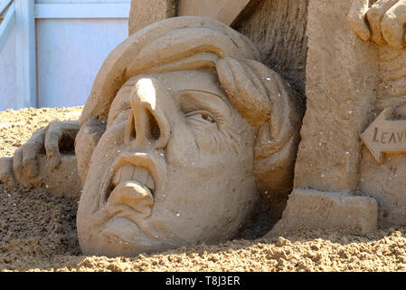 Weston-super-Mare, Somerset, UK. 14th May 2019. The theme of this year¡¯s annual sand sculpture festival is What If. Politicians featured in bizarre situations are President Trump, President Putin and Prime Minister May. Many of the sculptures have a topical theme, covering plastic waste, obesity and of course Brexit. These depict a sticky end for Theresa May. The festival runs until September. Credit: Mr Standfast/Alamy Live News - Stock Image