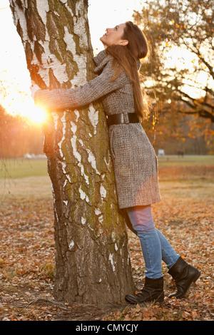 Germany, Berlin, Wandlitz, Mid adult woman hugging tree - Stock Image