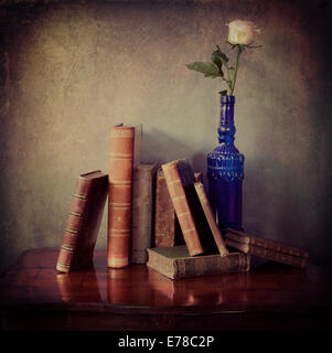 Interior still life, composition of antique books on a wooden table and a single pink rose in a blue  bottle with - Stock Image