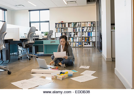 Designer working at laptop on floor in office - Stock Image