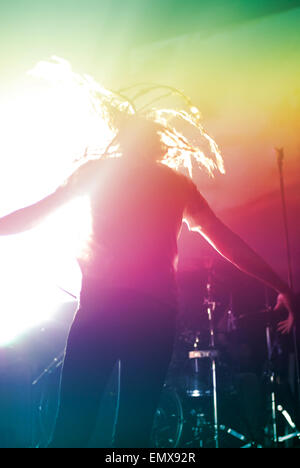 Anonymous or faceless rock star on stage, has turned away from audience to face drummer and is jumping or dancing, - Stock Image