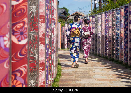 Arashiyama, Kyoto, Japan - September 18 2017: Two woman with kimonos walk through poles with traditional colourful - Stock Image