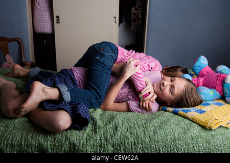 Two girls wrestling on the bed - Stock Image