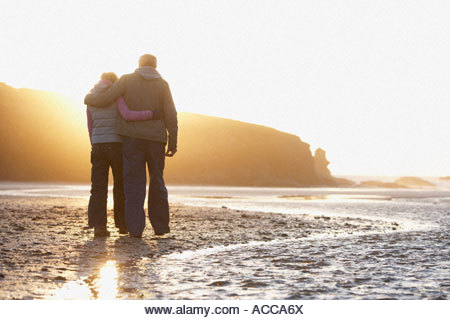 couple happily embracing walking down the beach - Stock Image