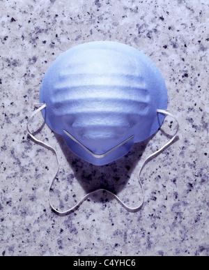 Un masque chirurgical bleu sur une surface sale - Image