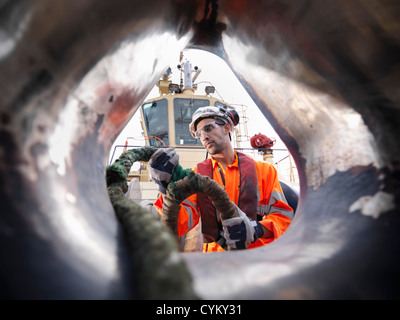 Tugboat worker pulling rope on deck - Stock Image
