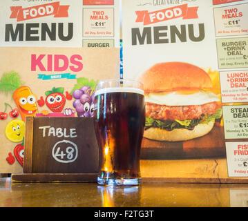 Pinte de bière avec des menus de nourriture dans un pub traditionnel en Angleterre, Royaume-Uni - Image