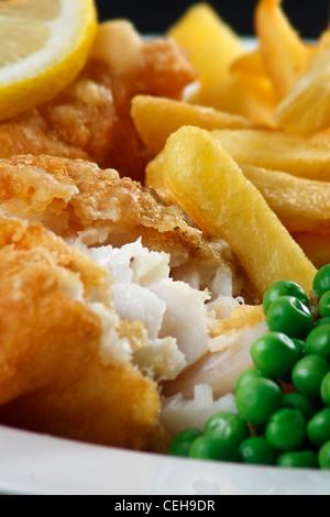 Gros plan de fish and chips avec des pois et une rondelle de citron. Un plat de bord de mer britannique traditionnel - Image