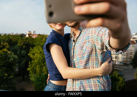Germany, Berlin, Young couple hugging and taking selfie with smart phone - Stock Image