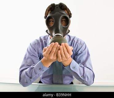Homme d'affaires assis portant un masque à gaz tenant ses mains sur sa bouche - Image