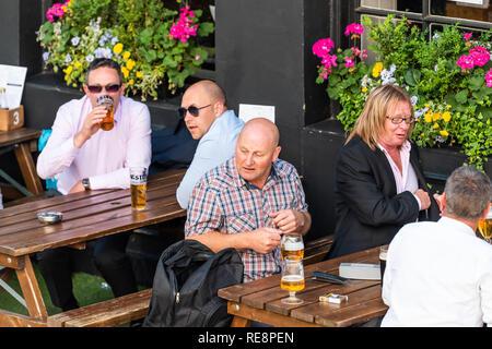 Londres, Royaume-Uni - 22 juin 2018: Personnes assises au pub Sawyers Arms boire une pinte de bière en verre à table en été - Image